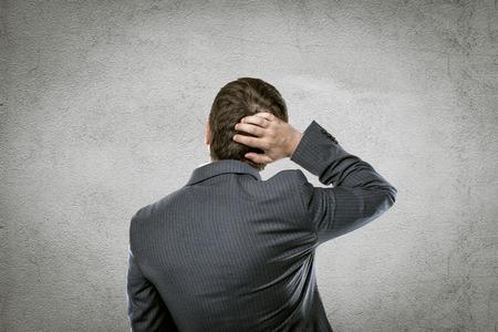 Portret van verwarde zakenman denken van innovatief idee op grijze muur.