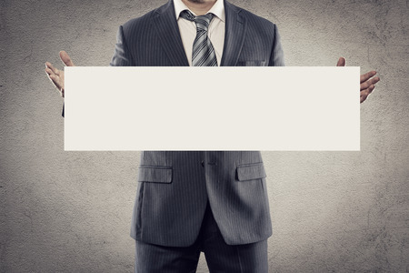 cartel: Portrait of young businessman in suit holding white sticker or signboard in his hands. Elegant man in business suit with tie advertising smth with blank paper for text message.