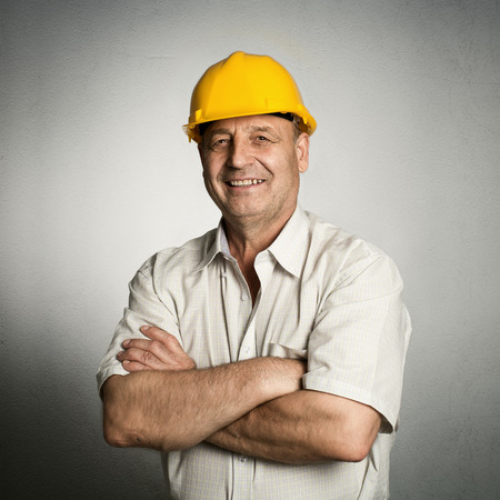 Portrait of happy mature architect in helmet standing with crossed arms. Male industrial inspector of 50s wearing uniform posing in studio