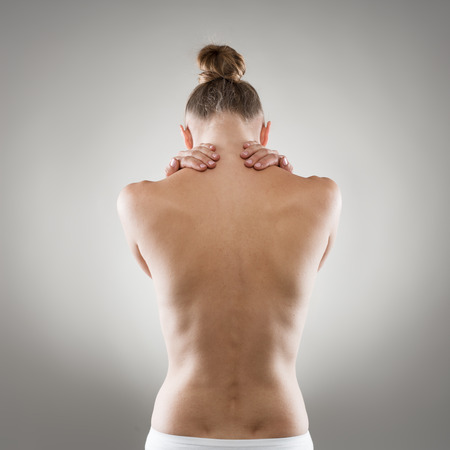 young girl nude: Spine and neck disease. Close-up of naked womans back suffering from muscle pain.