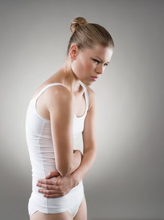 Red panties: Abdomen or menstruation pain. Young woman touching her abdomen in pain. Stock Photo