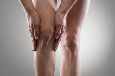 rheumatism: Female healthy legs. Woman touching her injured knee. Rheumatism or arthritis concept. Stock Photo