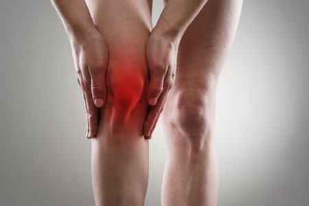 human knee: Tendon problems on woman leg indicated with red spot. Joint inflammation concept. Stock Photo