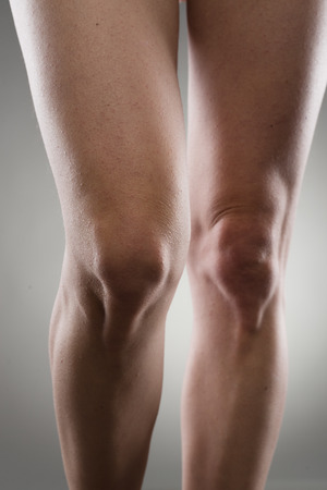 contracture: Close-up of healthy female legs over grey background. Knee joint care concept.