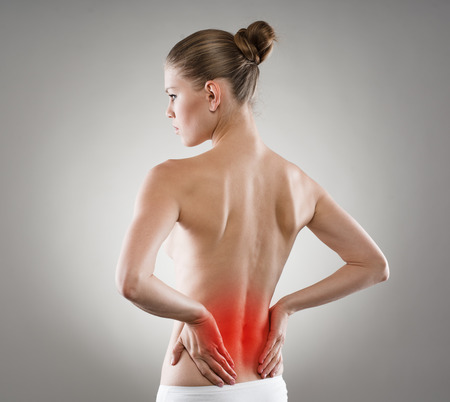 Backbone disease. Loin stretch shown with red spot on woman spine. Young female touching her painful back.