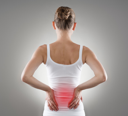 illness: Loin spasm. Young woman with hurt backbone. Spine inflammation, pain and therapy. Stock Photo