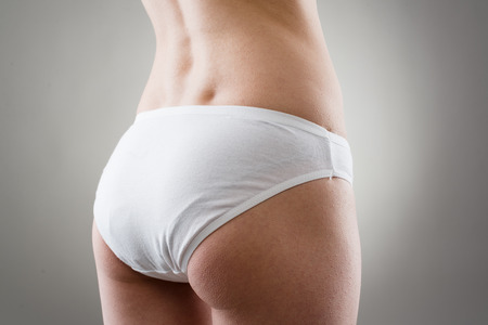 fat burning: Close-up of female buttocks. Liposuction and cellulite removal concept.