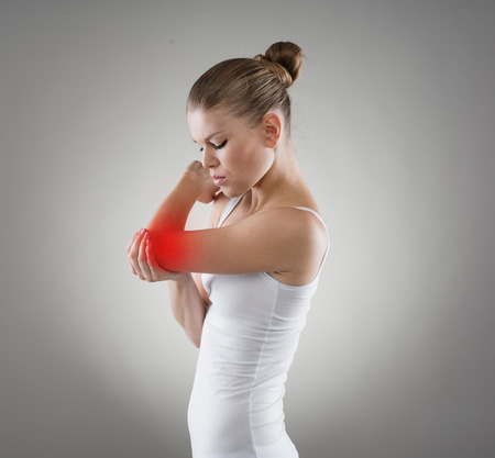 osteoarthritis: Hembra joven con dolor en el codo. La osteoartritis o concepto gota conjunta. Foto de archivo