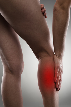 calf pain: Close-up of young female touching her leg calf in pain over grey background. Muscular hurt or cramp concept. Stock Photo