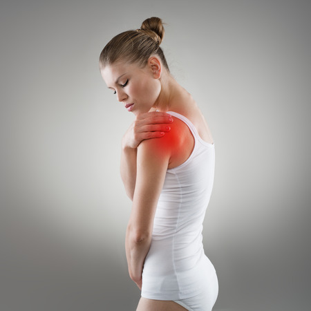 Young woman having pain in shoulder. Joint illness or fracture treatment concept.