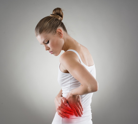 red  stone: Young female touching her left side in pain. Kidney inflammation and therapy. Medicine and health care concept.