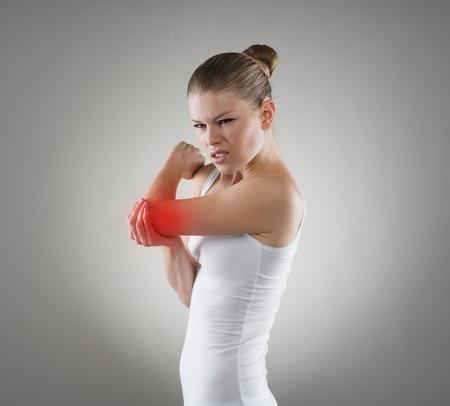 luxacion: Retrato de la mujer cauc�sica joven que sufre de luxaci�n o dislocaci�n del codo. Concepto de fracturas de huesos. Foto de archivo