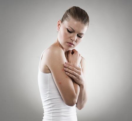jeuken: Portret van een jonge vrouw die lijdt aan jeuk na muggenbeten. Dermatologie, allergische huid behandeling concept.