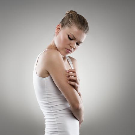 Giovane femmina graffiare il suo braccio eruzioni cutanee. Donna con dolore eczema della pelle. Medicina e concetto di assistenza sanitaria. Archivio Fotografico