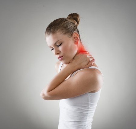 Young woman suffering from neck cramp. Nape pain and treatment concept.