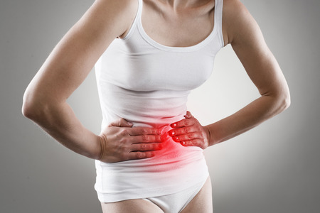 Young female having stomachache. Chronic gastritis. Ulcer. Abdomen bloating concept. Stock Photo