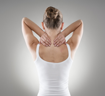 massage: Portrait of young woman massaging her painful neck over grey background. Muscle spasm and backache concept.
