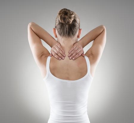 musculo: Retrato de mujer joven masajear su cuello doloroso sobre fondo gris. El espasmo muscular y el concepto de dolor de espalda.