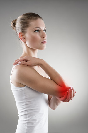 codo: Inflamación de las articulaciones indica con mancha roja en el codo mujer. Dolor en el brazo y el concepto de lesión.