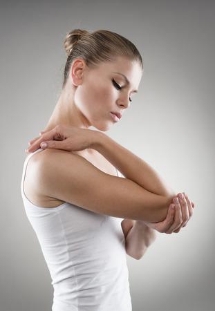 luxacion: Retrato de mujer joven que tiene dolor en las articulaciones y masajear su codo sobre fondo gris. Foto de archivo