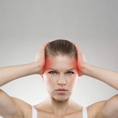 dizziness: Head pain or injury. Young stressed female suffering from dizziness or tension. Medical treatment and health care concept. Stock Photo