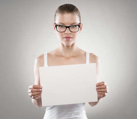 relaciones publicas: Mujer hermosa en anteojos que promueven smth con el cartel blanco. Las relaciones públicas y el concepto de comunicación. Foto de archivo