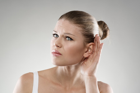 deafness: Deafness and ear disease. Young woman having hearing problems. Health care and hospital treatment concept. Stock Photo