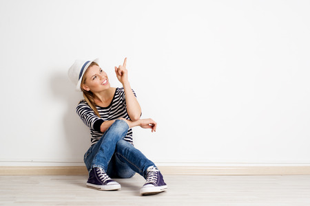 furnish: Beautiful woman pointing at copy space on empty wall in new house. Young smiling casual girl sitting on wooden floor and showing smth with her finger.