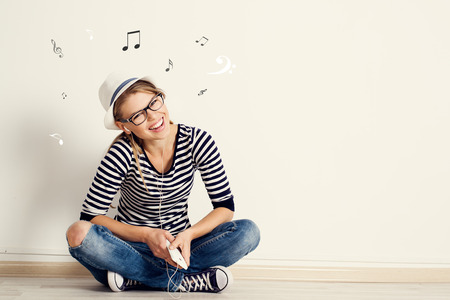 music score: Portrait of happy female listening musical composition in earphones with sheet music and clef drawn on the wall. Young pretty Caucasian woman sitting on wooden floor in her house.