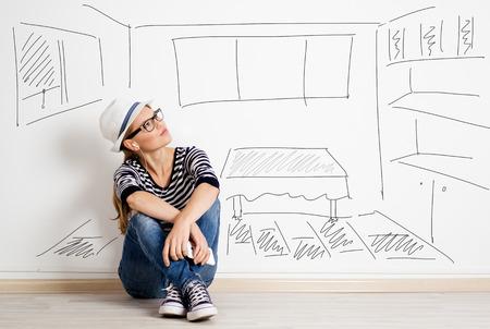 描かれたリビング ルーム背景上のヘッドセットの夢の女性。彼女の新しいマンションを供給する若いきれいな女性の思考。 写真素材