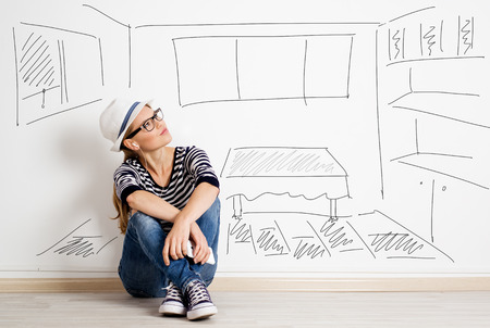 Dreaming woman in headset over drawn living room background. Young pretty female thinking of furnishing her new apartment. Stockfoto