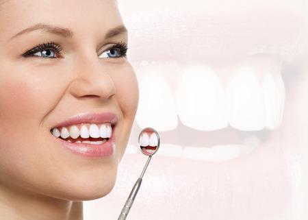 Frais sourire. Blanchissement dentaire. Chèque orale jusqu'à. Portrait de jeune femme gaie examiner ses dents avec miroir dentaire.