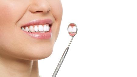Les soins dentaires et d'inspection. Close-up de la femme saine sourire blanc avec miroir. Dentiste visite concept.