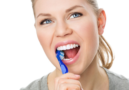 oral hygiene: Oral hygiene and prevention. Portrait of young Caucasian female cleaning her teeth and tongue, isolated on white.