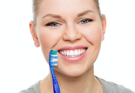 cavity: Dental cure. Cavity protection. Close-up portrait of happy female with toothy smile holding brush over white . Stock Photo