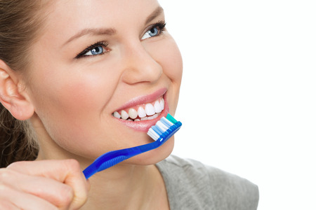 disease prevention: Teeth washing. Disease prevention. Portrait of young Caucasian female model with beautiful white smile brushing teeth.