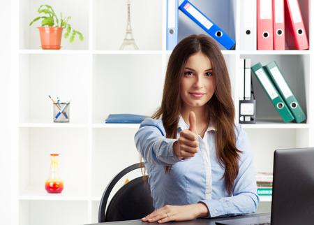 agente comercial: Acertado joven especialista en bienes ra�ces femenina que muestra el pulgar hacia arriba. Concepto de �xito en los negocios. Especialista sonriente mujer sentada en el escritorio en la oficina.