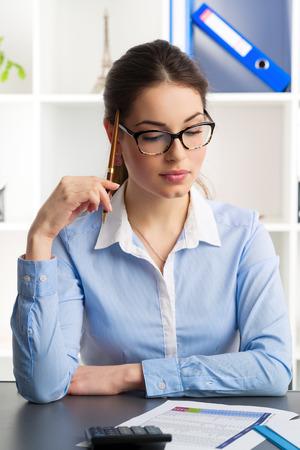 bookkeeper: Tenedor de libros de sexo femenino joven calcular empresa de p�rdidas y ganancias. Analista financiero Atractiva mujer sentada sobre los documentos en el lugar de trabajo.
