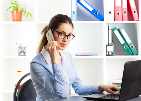real estate agency: Telemarketing woman. Pretty female consultant talking on phone sitting in front of laptop computer. Stock Photo