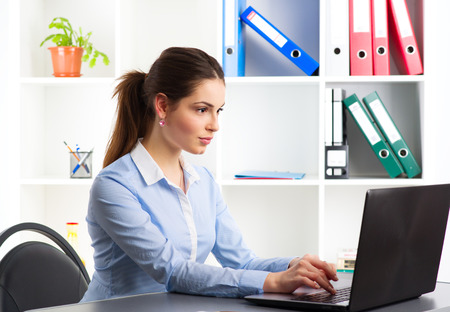 sales person: On-line job. Young woman communicating with partners via internet. Confident sales person working at laptop in the office. Stock Photo