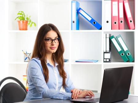 Gerente general femenino joven que trabaja en la computadora en su agencia. Concepto de nuevos proyectos, ideas y éxito.