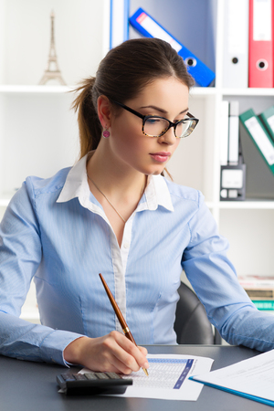 the bookkeeper: Portrait of pretty businesswoman signing financial document in the office. Young concentrated accountant sitting with ballpoint at the table. Stock Photo