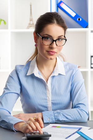 auditor: Portrait of smiling woman auditor sitting at the table reviewing corporate accounting documents in the office. Young smart business woman wearing eyeglasses.