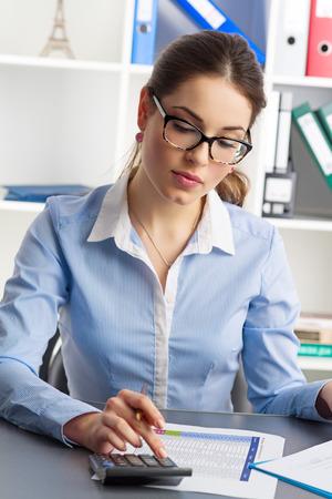 監査女性概念。若い実業家計算年間予算。オフィスで働く金融アナリスト。