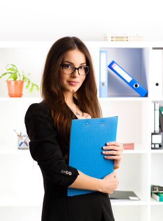 spokesperson: Portrait of beautiful businessperson standing with document file at her workplace. Young friendly real estate agent wearing eyeglasses working in the office. Stock Photo