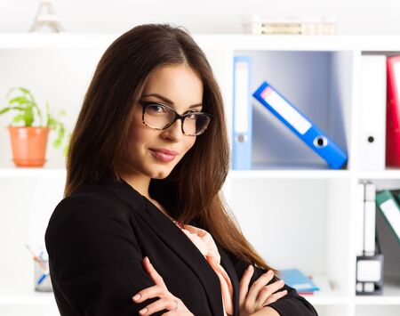 finance director: Portrait of smiling confident female company director wearing eyeglasses and business suit. Concept of competence and professionalism.