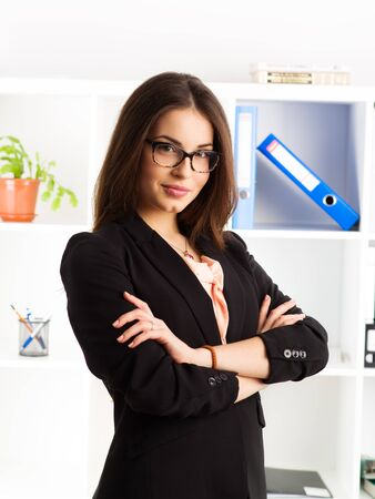sales manager: Portrait of pretty businessperson in eyeglasses posing in bureau. Young successful female sales manager at work.