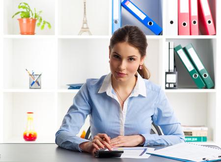 concepto equilibrio: Consultor de cr�dito hembra joven calcular la tasa de inter�s que se sienta en el escritorio en la oficina. Mujer financista inteligente an�lisis de las estad�sticas de pr�stamos.