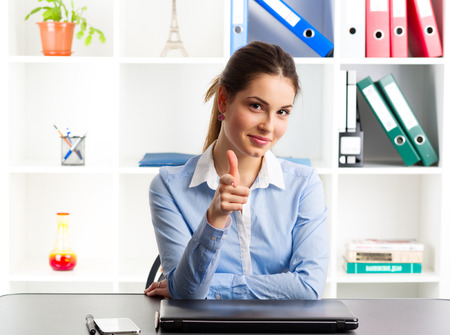 amiable: Portrait of smiling businesswoman loan agency expert showing thumb up. Amiable female manager sitting at the desk with laptop and phone. Stock Photo