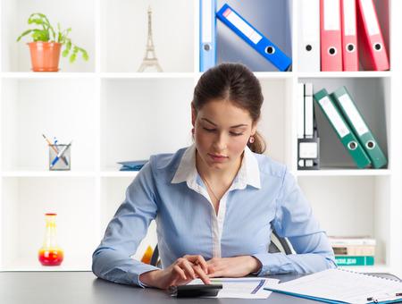 evaluacion: Economista Mujer que usa la calculadora para la empresa corre el riesgo de evaluación. Joven mujer auditor concentrado trabajando en la oficina.